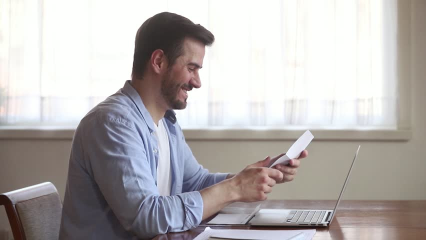 Happy young man open envelope holding paper mail letter reading good news feel excited overjoyed winner got job contract, smiling euphoric entrepreneur receive salary taxes refund offer in document | Shutterstock HD Video #1029331763