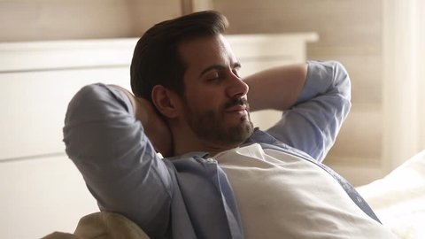Happy lazy young man relax daydream meditate sit on comfortable sofa at home in living room, calm guy rest breathing fresh air having nap with eyes closed feel peace of mind, no stress free relief