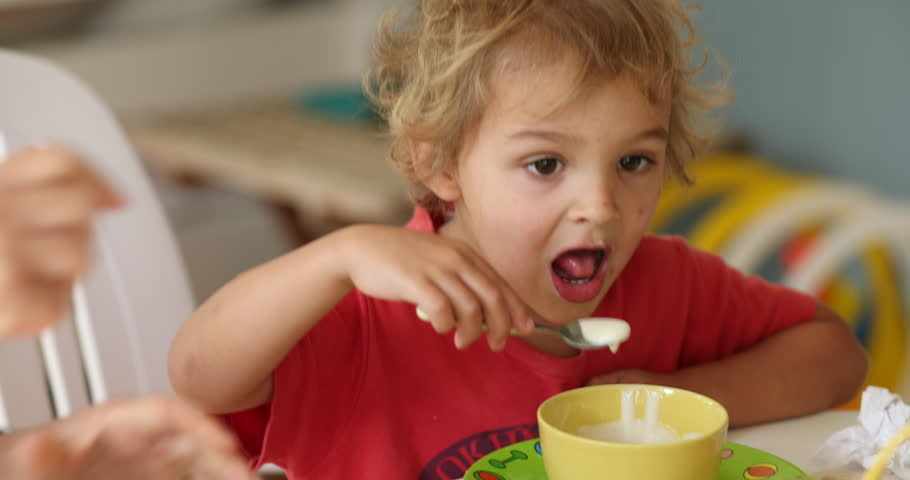 Toddler baby boy eating yogurt at home in casual candid family scene   Shutterstock HD Video #1029408263