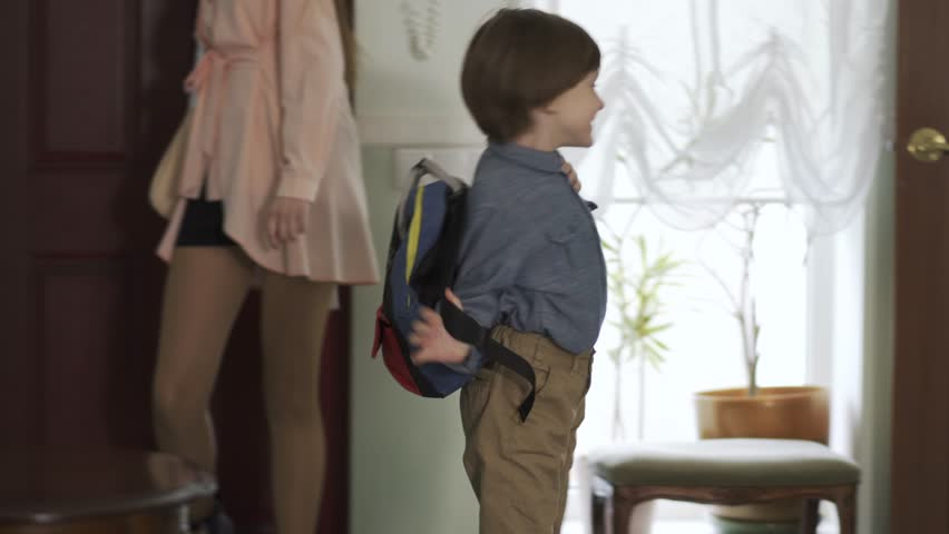 Pretty teenage girl and little brother with backpack entering the house. Children are happy to back home, boy is smiling. Kids as adults | Shutterstock HD Video #1029412073
