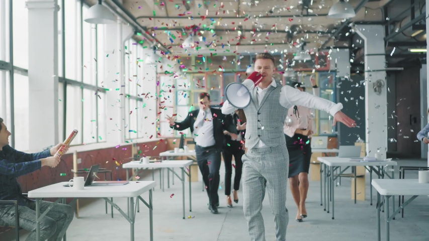 A young businessman goes to the office and starts dancing, holding a megaphone. Colleagues join, dance with him and blow up flappers with confetti. Creative coworking. Office holiday. Corporate party | Shutterstock HD Video #1029418733