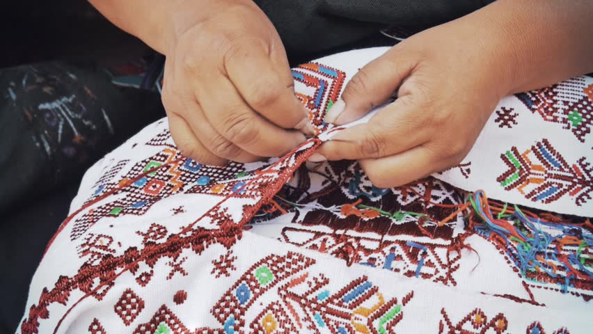 Mayan woman embroidering fabric with a handmade yarn
