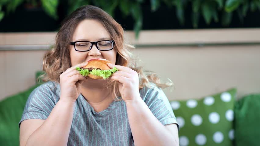 Portrait of pleased smiling fat overweight woman eating appetizing burger looking at camera