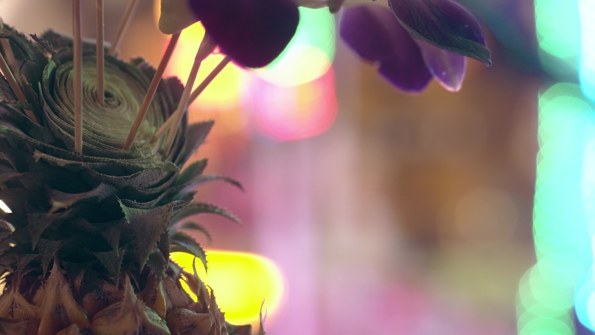 part of delicious tropical pineapple against gleaming bright blue pink yellow neon lights close view