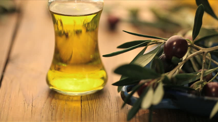 bottle of olive oil with olives rolling in foreground