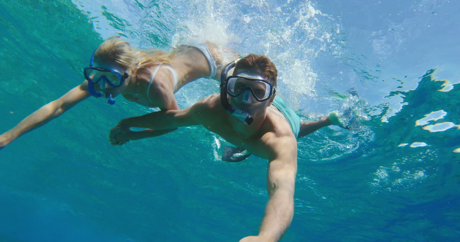 POV shot of young attractive couple diving down and snorkeling together in tropical ocean water, summer vacation fun | Shutterstock HD Video #1029503363