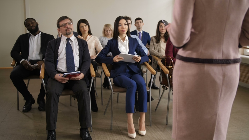 Interested diverse multi ethnic team of employees taking part at corporate business meeting. Group of co-workers intently listening to executive manager presenting new company's strategy | Shutterstock HD Video #1029510773