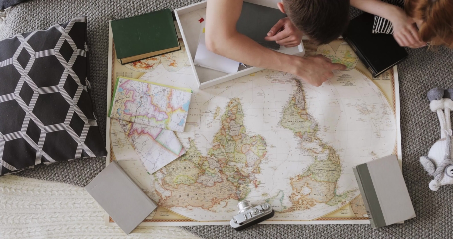 Young couple girl and guy are planning travelling route on the car laying in bed and pointing places for visit on a map in South and North America using red flag pins. #1029518783