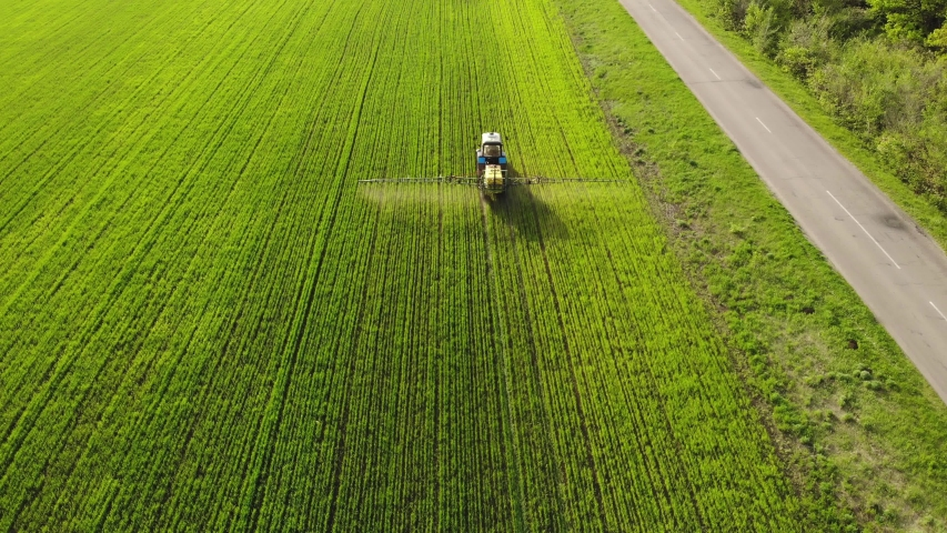 Aerial view of farming tractor spraying on field with sprayer, herbicides and pesticides at sunset. Farm machinery spraying insecticide to the green field, agricultural natural seasonal spring works. | Shutterstock HD Video #1029535583