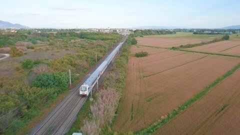 Aerial tracking of a passenger train in the countryside.