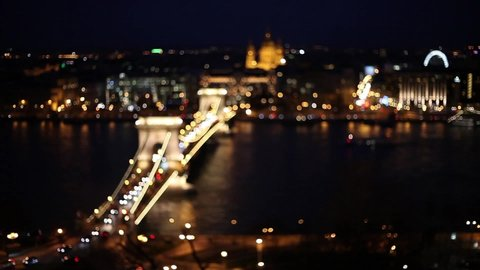 Car traffic night city lights blurred bokeh background. Video of night city road. Cars and bus moving on road on bridge in night. Budapest, Hungary