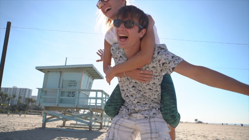 Piggy back at the beach. Young couple having fun at Santa Monica beach Los Angeles. Slow motion  | Shutterstock HD Video #1029605183