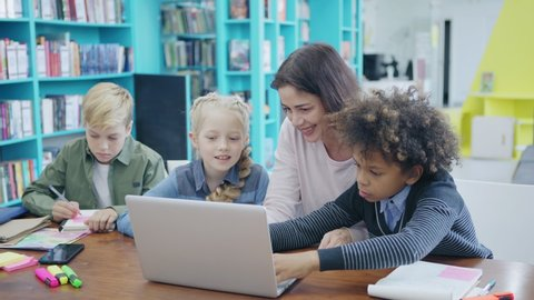Female teacher and group of elementary students sitting at desk in classroom. Tutor and two kids mixed race schoolboy and blonde girl, doing tasks on laptop while another boy writing in notepad nearby