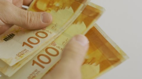 Counting 100 shekel bills - close up of Israeli money