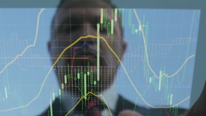 Reflection of the face of a businessman in a tablet that looks financial charts | Shutterstock HD Video #10297883