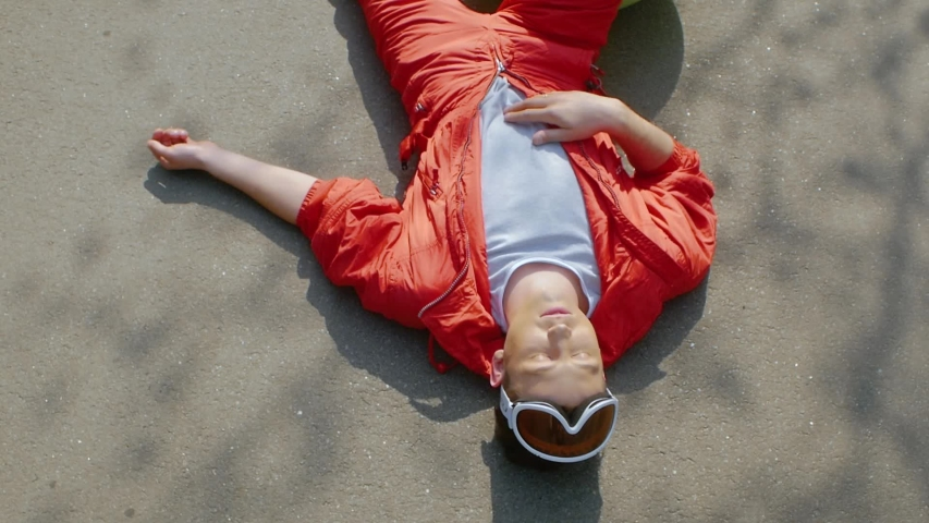 The guy lay on the asphalt road in the red jacket. Attractive guy wearing ski goggles on a background of ground | Shutterstock HD Video #1029790973