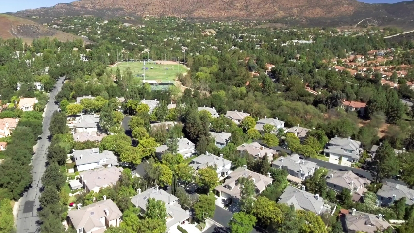 Aerial, drone shot, over a neighborhood of houses, at a Valley, in the LA suburbs, on a sunny day, in Los Angeles, California, USA | Shutterstock HD Video #1029831293