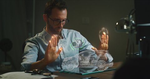 An engineer is designing an electric car using sophisticated and futuristic technology programs with augmented  realty holography in his creative studio