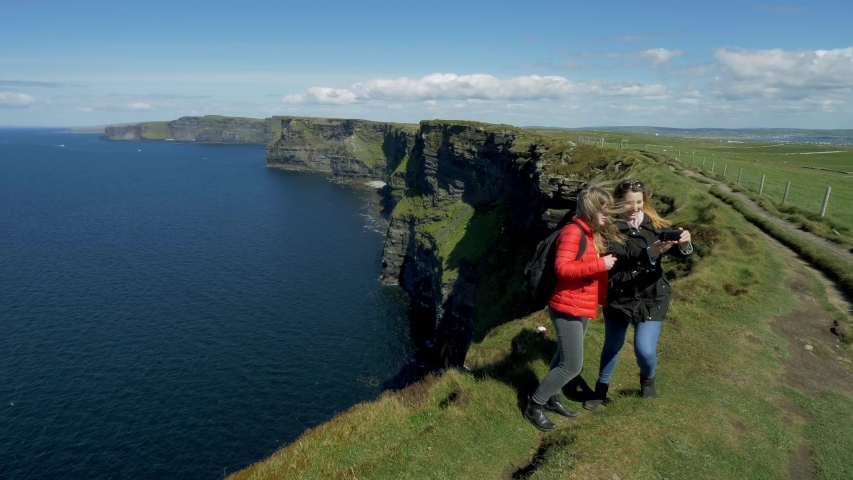 Two girls at the famous Cliffs of Moher in Ireland   Shutterstock HD Video #1029989903
