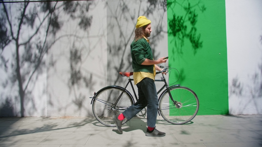 Side shoot of hipster in colorful outfit with classy bicycle using smartphone device, funny Hispanic male always online in social media application and connected in network at sunny day time | Shutterstock HD Video #1029993233