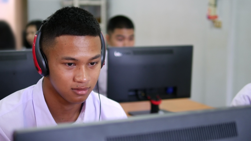 Asian high school male students wearing headphones are laughing and enjoying social media in computer class.   Shutterstock HD Video #1029995423