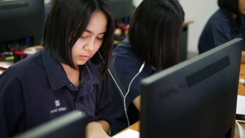 Asian high school female student is working by writing on paper and using searching from a desktop computer during computer study hours   Shutterstock HD Video #1029995663
