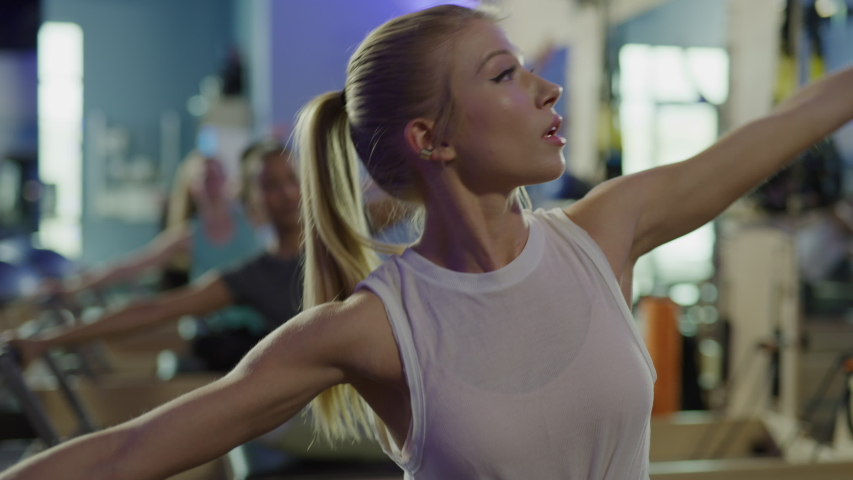 Close up of woman stretching arms while sitting on pilates reformer exercise machine / Lehi, Utah, United States | Shutterstock HD Video #1030010843