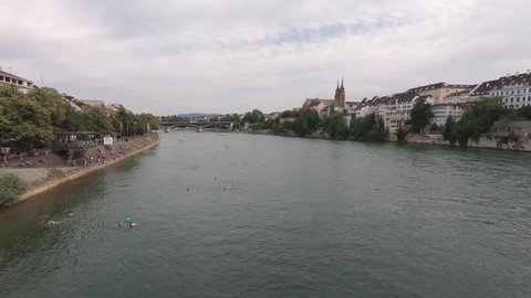 rhine in summer in Basel with people swimming
