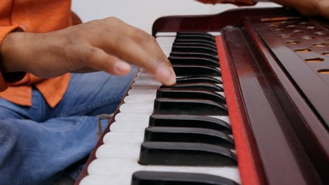 Indian musician playing keyboard of harmonium.