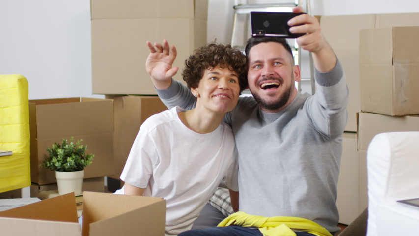 Panning shot of delighted middle-aged Caucasian couple sitting on floor between cardboard moving boxes after relocation and taking selfies with smartphone, hugging, smiling, waving and posing together   Shutterstock HD Video #1030095113