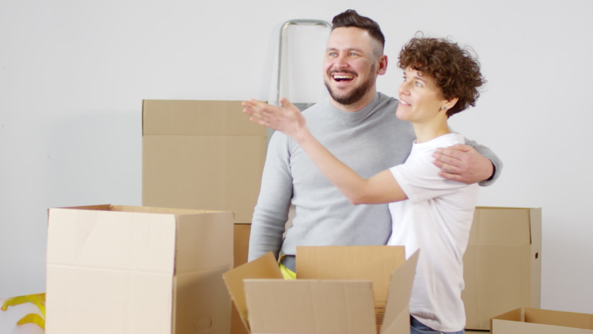 Medium shot of delighted affectionate middle-aged Caucasian couple bringing in cardboard boxes, then embracing and admiring their new home, laughing and looking around with excitement   Shutterstock HD Video #1030097963