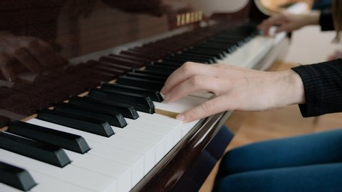 A woman touches the keys with her fingers. Close on the piano keys. Female hands playing the piano. Musician pianist plays the piano. I enjoy music, jazz.