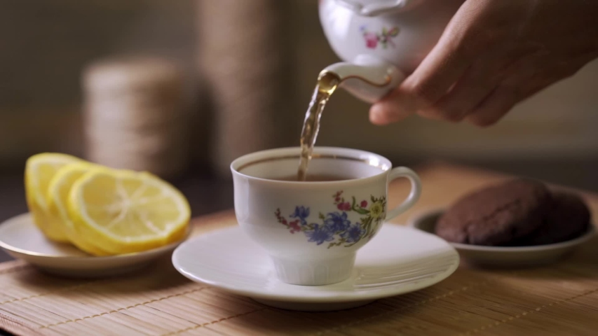 Tea being poured into tea cup. Dessert and hot drink. Lemon slices. Tea time. | Shutterstock HD Video #1030192433