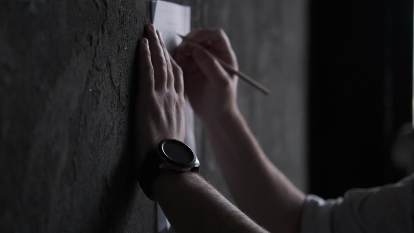 A man makes notes in a document by pressing a sheet of paper against a wall. | Shutterstock HD Video #1030199933
