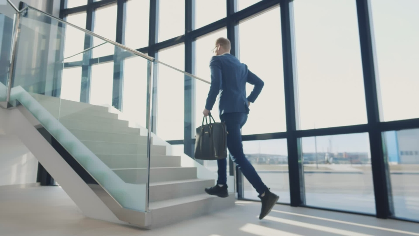 Businessman walking up the stairs hastily. In his hand is a brown leather briefcase