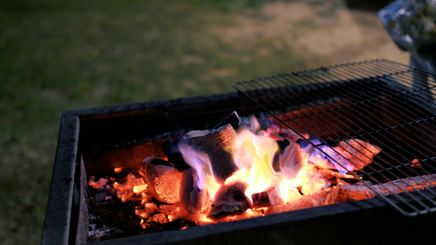 Glowing barbecue embers, fire charcoal in stove for cooking and grilling food or outdoors barbecue. Royalty high-quality free stock footage of embers burning with red and yellow flame    Shutterstock HD Video #1030223063