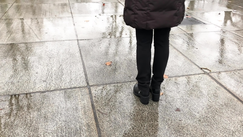 Woman walking on a wet surface with city park reflections. Isolation concept. | Shutterstock HD Video #1030228973