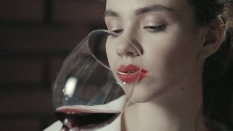 Portrait pretty woman holding wineglass and sniffing red wine. Close up beautiful woman drinking red wine from glass. Young woman tasting red wine