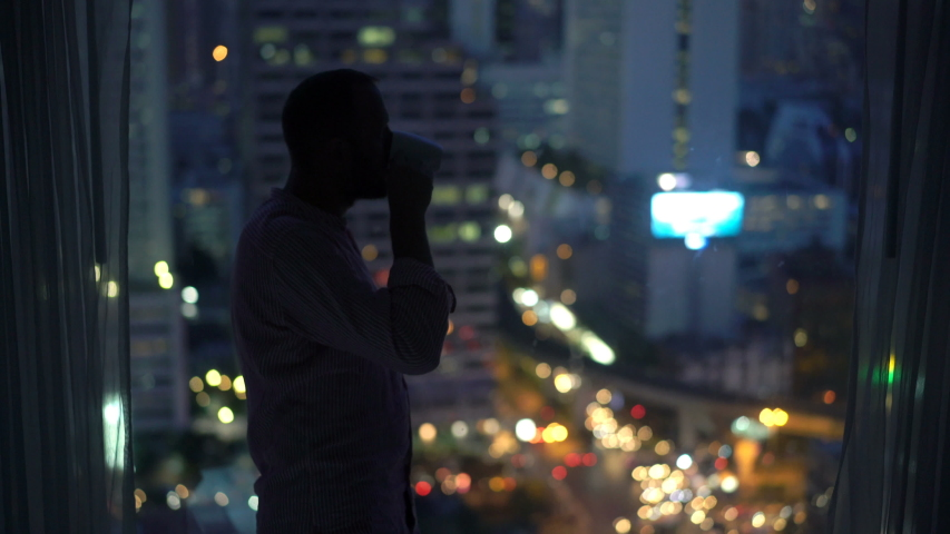 Man drink and admire city at night view standing by window at home | Shutterstock HD Video #1030263113