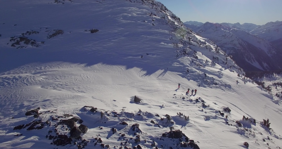 Aerial view of backcountry skiing on sunny day in beautiful big-mountains in British Columbia, Canada,    Shutterstock HD Video #1030283483
