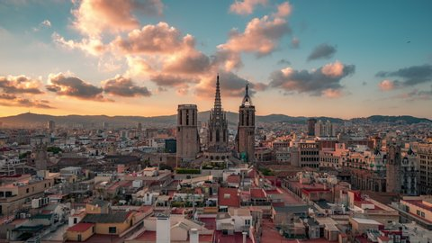 Barcelona - Cathedral, Barri Gothic Quarter, Time lapse. Cumulus sunset clouds over old city districts. Panoramic view, buildings roofs.