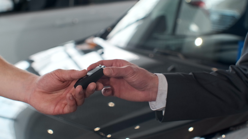 Male hand gives a car keys to man hand in the car dealership close up. Unrecognized auto seller and a woman who bought a vehicle shake hands.