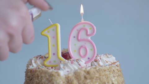 Sweet sixteen birthday celebration with cake and candles shaped like number sixteen. Hand with lighter ignites candles on top of cake at party.