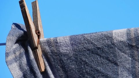 Close up on wooden clothespin peg waving in the wind, holding patterned fabric shirt to washing line set against blue sky.