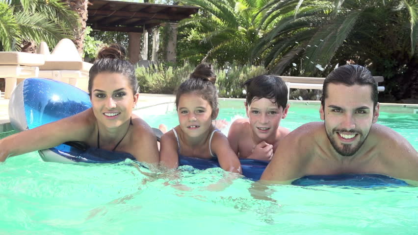 Slow motion sequence of family lying on airbed in swimming pool and swimming towards camera.Shot on Sony FS700 at frame rate of 100fps