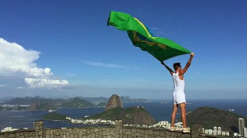 Athlete in old-fashioned white sports uniform standing with Brazilian flag at city skyline overlook in Rio de Janeiro Brazil