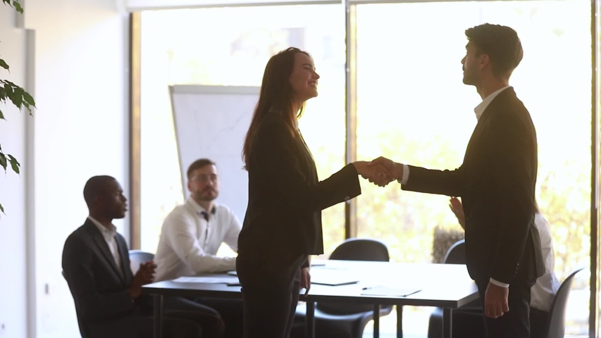 Happy manager handshake promote praise female employee for good work in office, overjoyed woman employee get appreciated rewarded with team applause shake hand of boss, respect recognition concept  | Shutterstock HD Video #1030504763