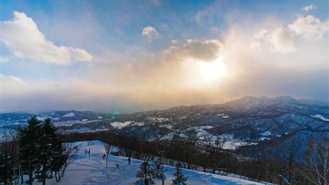 Clouds roll across the mountains in a beautiful winter landscape time lapse.. Scenic beauty of a night view of Mt. Moiwa, near Sapporo, the biggest city in Hokkaido. Popular ski resort destination.