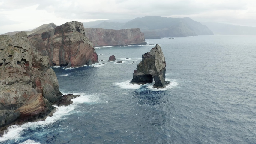 Forwarding aerial view above the coastline Of Madeira With High Cliffs Along The Atlantic Ocean waves breaking against the rocky terrain.