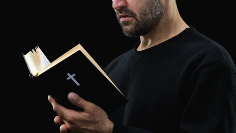 Bearded man reading holy bible, praying God against dark background, psalm